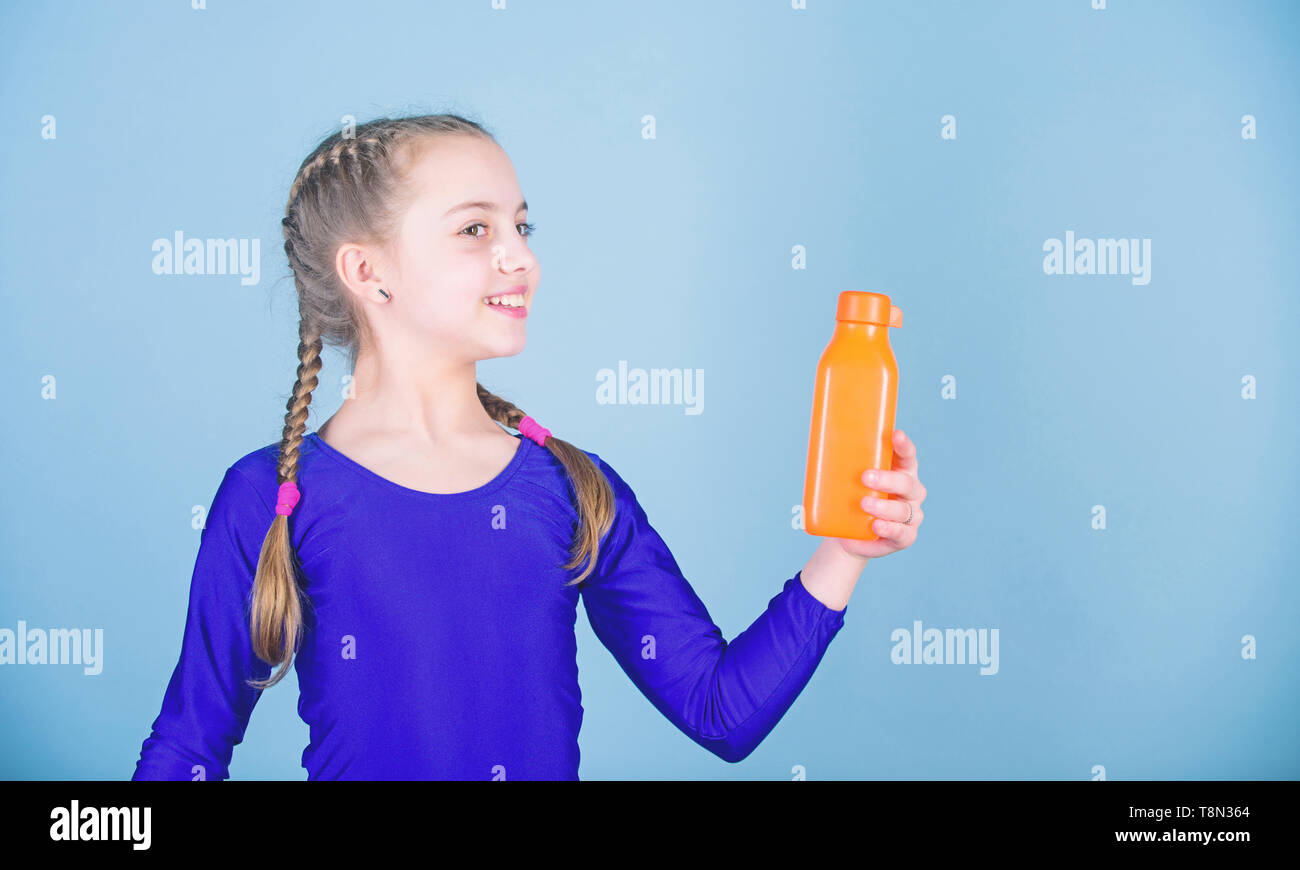 Water balance and hard gym training. Drink more water. Keep water bottle with you. Quench thirst. Child feel thirst after sport training. Kid cute girl gymnast sports leotard hold bottle for drink. - Stock Image