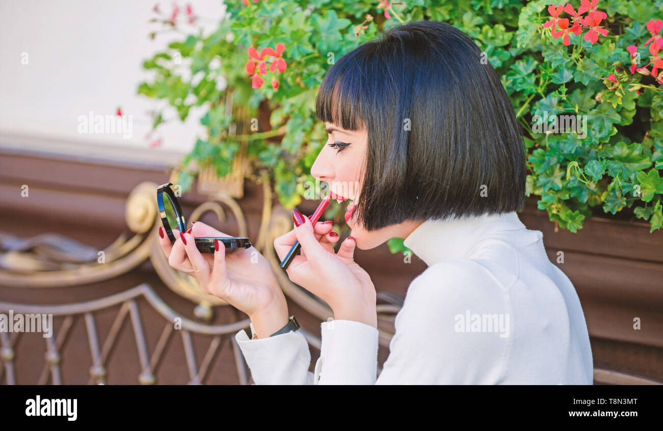 Girl brunette with lipstick looking in mirror check her makeup appearance. Girlish secrets concept. Woman making makeup with pocket mirror. Check if everything is right before date. Makeup concept. - Stock Image