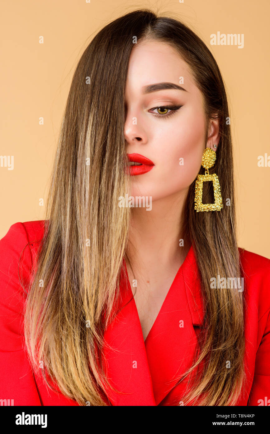 Impeccable makeup and perfect jewelry. Woman wear glamorous earrings. Fashion trend. Jewelry shop. Girl model long hair demonstrating golden jewelry earrings. Expensive accessory. Fashionable jewelry. - Stock Image