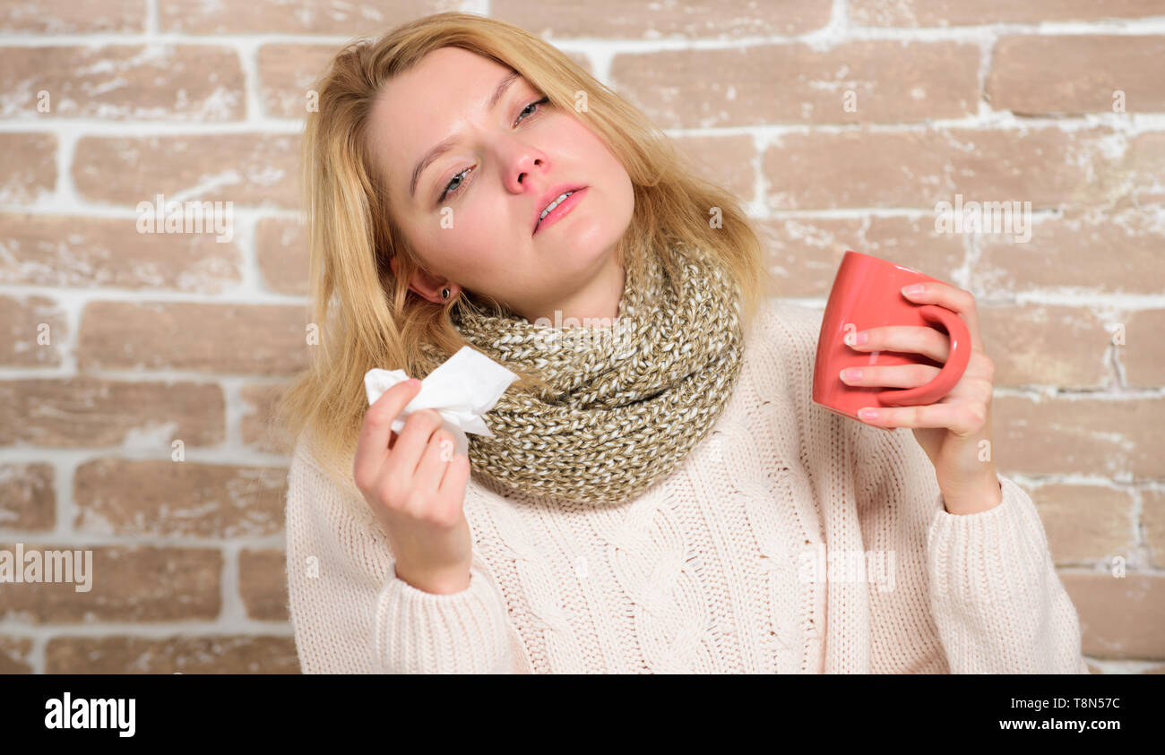 Cold and flu symptoms. Sick woman with sore throat drinking cup of warm tea. Pretty girl with nasal cold suffering from headache. Cute woman caught terrible cold virus. A tea cure. - Stock Image