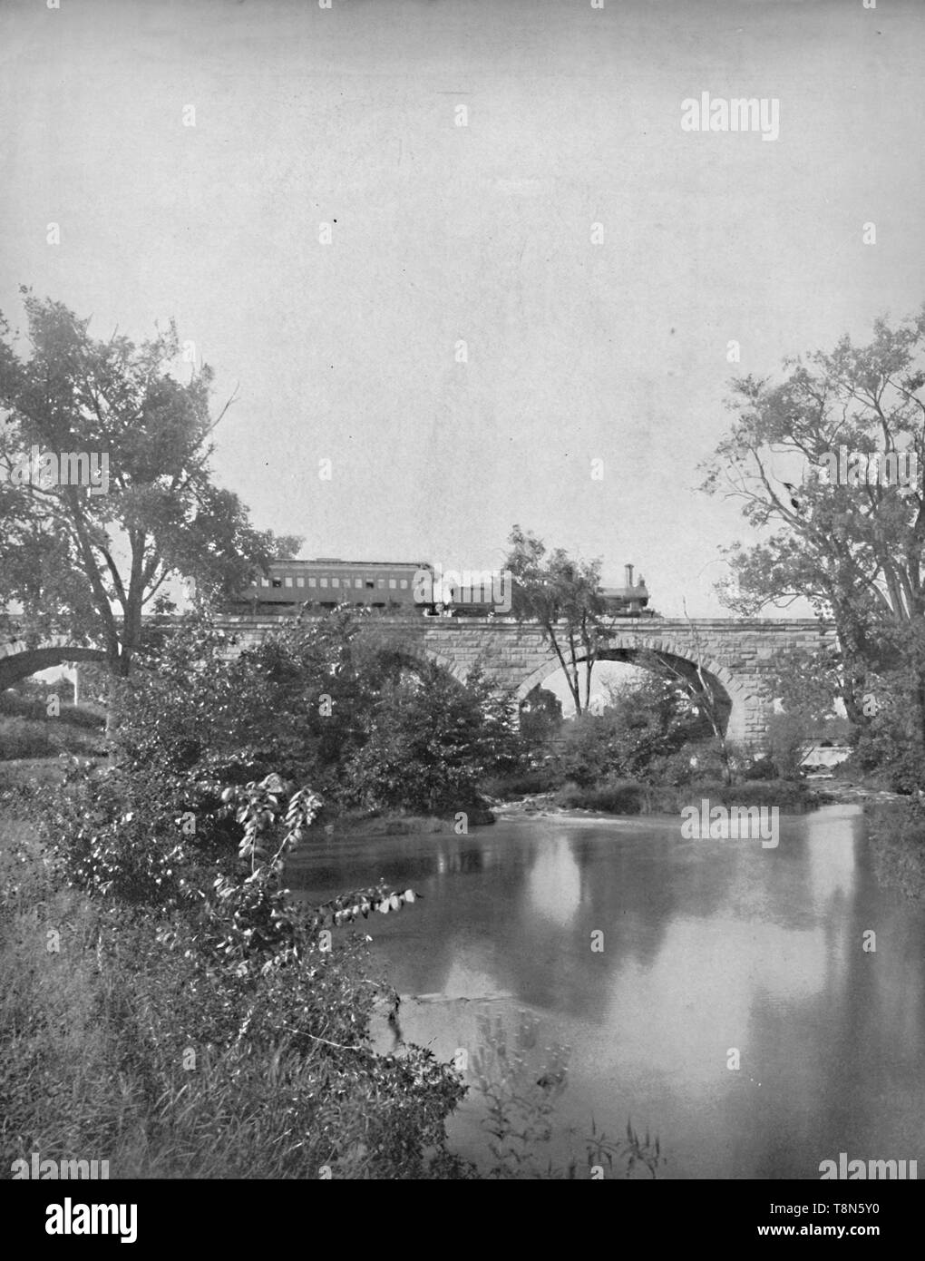 """'Mill Creek Bridge, Pennsylvania Railroad', c1897. Locomotive pulling carriage on stone arch bridge over Mill Creek. From """"A Tour Through the New World America"""", by Prof. Geo. R. Cromwell. [C. N. Greig & Co., London, c1897] - Stock Image"""