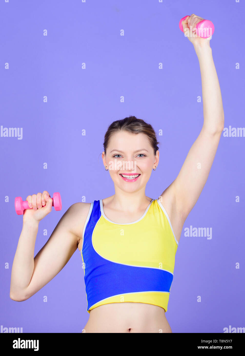 Exercising with more energy. Healthy lifestyle concept. Woman exercising with dumbbells. Fitness exercises with dumbbells. Workout with dumbbells. Girl hold dumbbells. Biceps exercises for female. - Stock Image