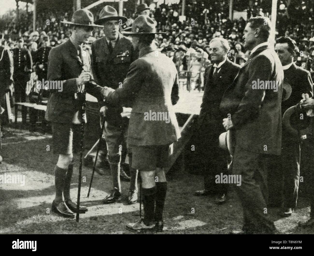 """'At the Parade of Boy Scouts and Girl Guides, Adelaide, Australia: The King gives the Scout Handshake, 1927', 1937. His Royal Highness The Duke of York 1920-1936 became King George VI on 11 December 1936. From """"George VI, King and Emperor"""", by Major J. T. Gorman [W. & G. Foyle Ltd., London, 1937] - Stock Image"""