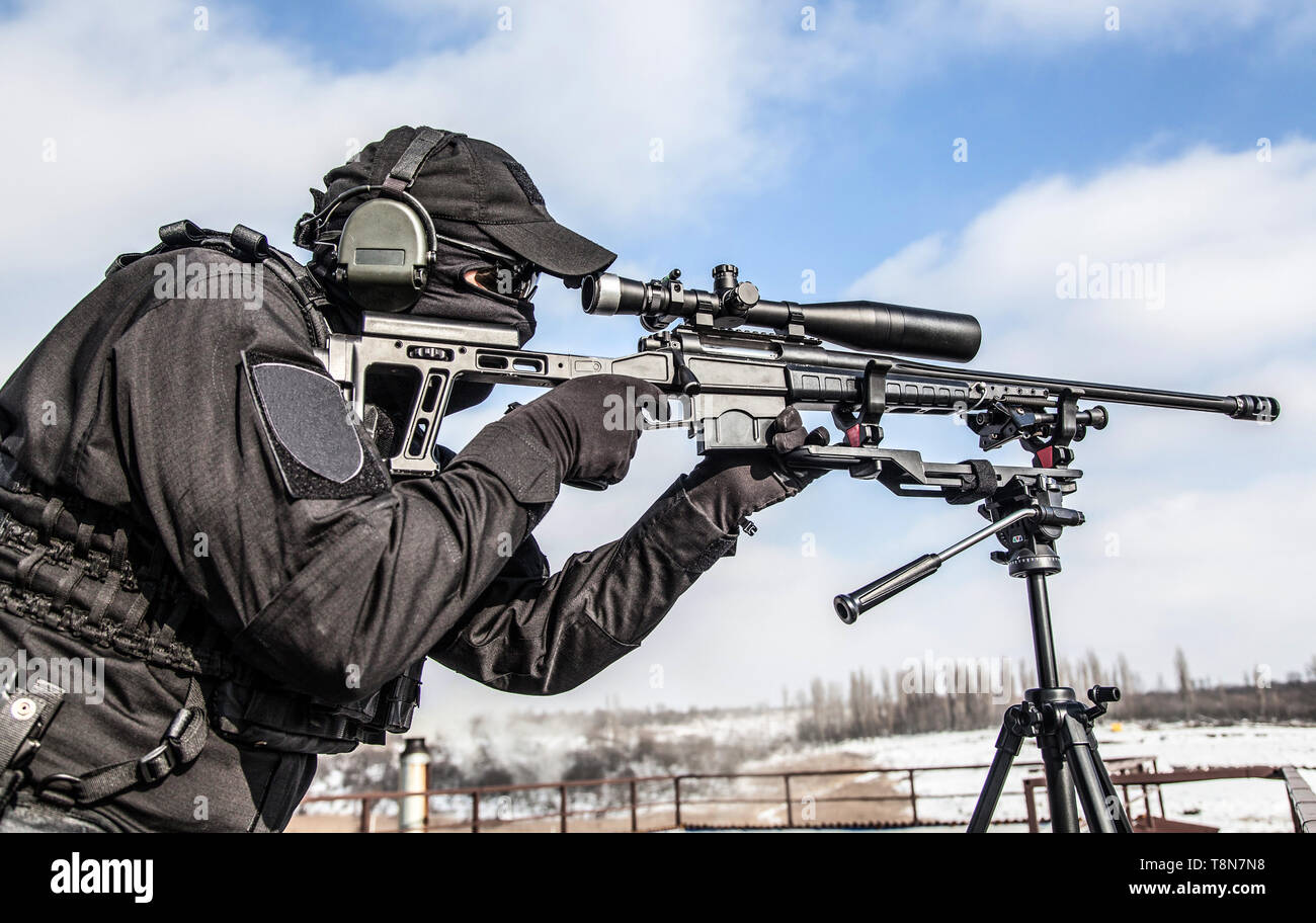 Equipped police SWAT sniper shooting with rifle - Stock Image