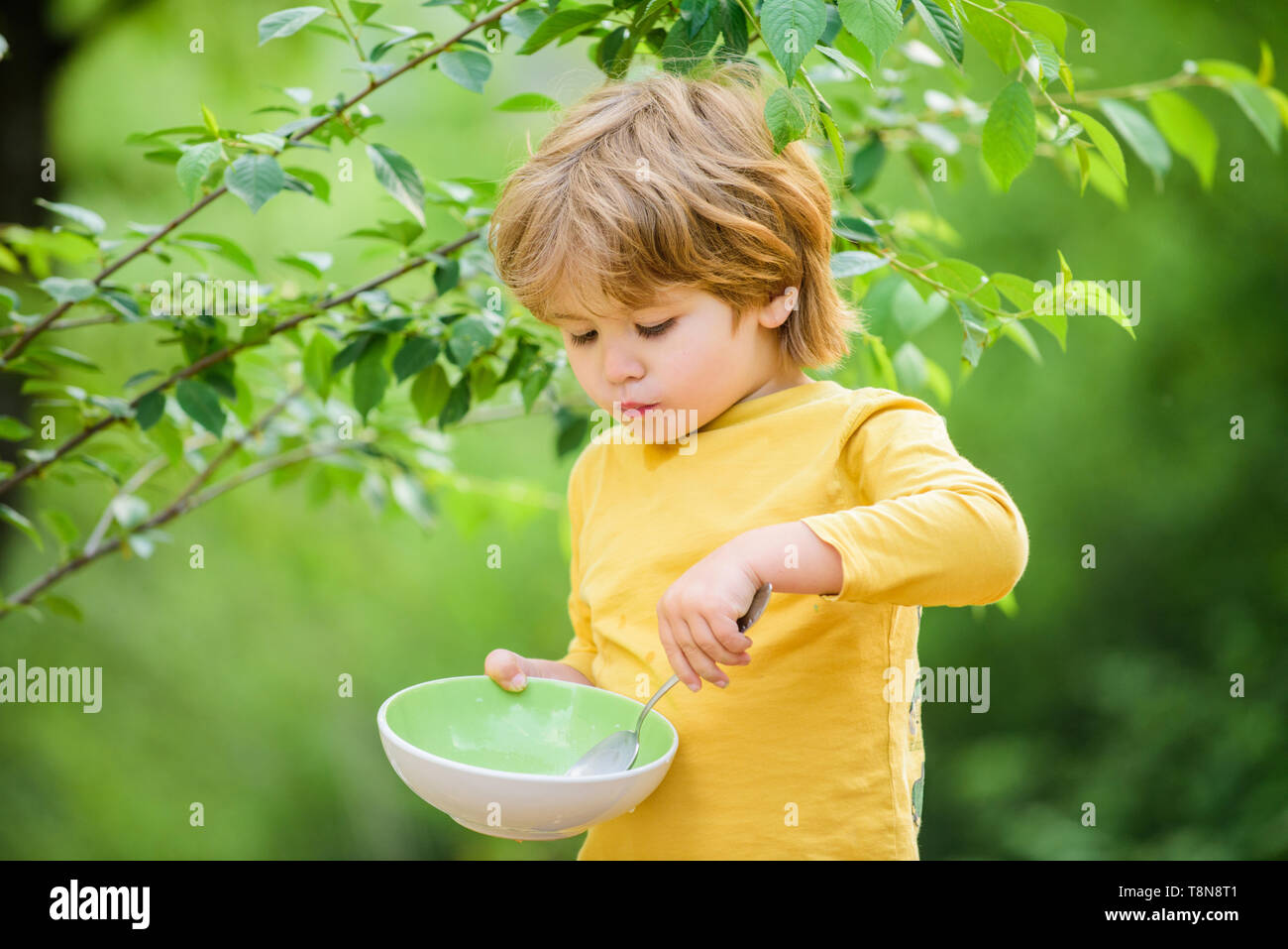 Small Boy Eating Outdoor Child Development Little Boy Eat Healthy Food Childhood Happiness Healthy Food And Dieting Family Day Son And Eating Milk Porridge Cereal For Breakfast Good Morning Stock Photo