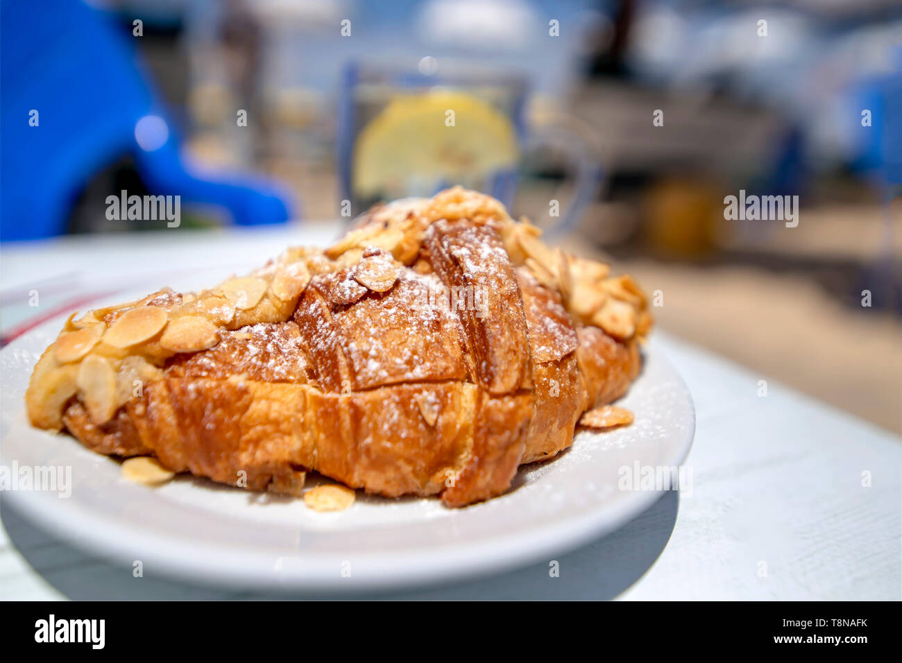 Croisson dusted with almonds and powdered sugar close-up on a blurred background. - Stock Image