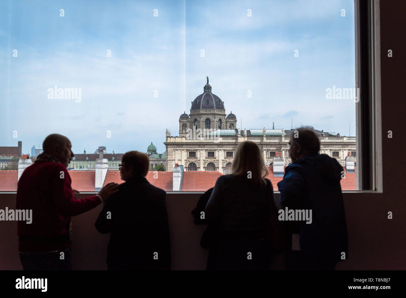Rear view of four people inside the Leopold Museum in Vienna looking out at city buildings, Austria. Stock Photo