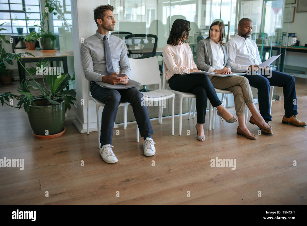 Job applicants sitting in an office waiting to be interviewed - Stock Image