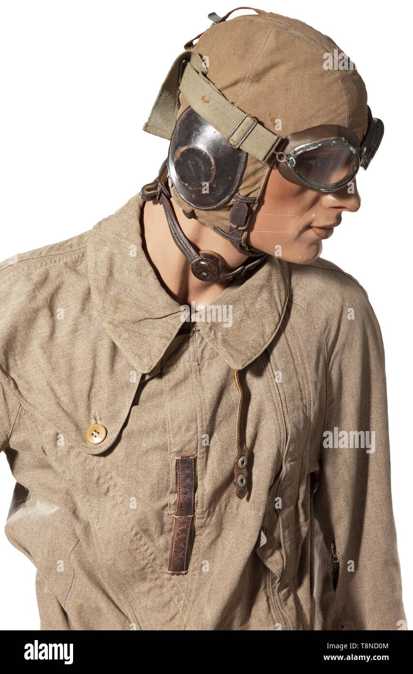A uniform ensemble for a pilot, summer outfit Summer flight helmet with larynx microphone, aviator goggles with tieback. Summer combination with 'Ri-Ri' zip closures and 'Prym' buttons, arm compass, brown leather belt with aluminium buckle and pistol holster. Lined leather boots with lateral zip closures and heating connections. The uniform is mounted on a movable mannequin with a martial profile. All parts with light signs of wear, mostly with maker or requisition markings. A beautiful ensemble for a typical aviator's summer outfit. historic, historical, Air Force, branch , Editorial-Use-Only - Stock Image