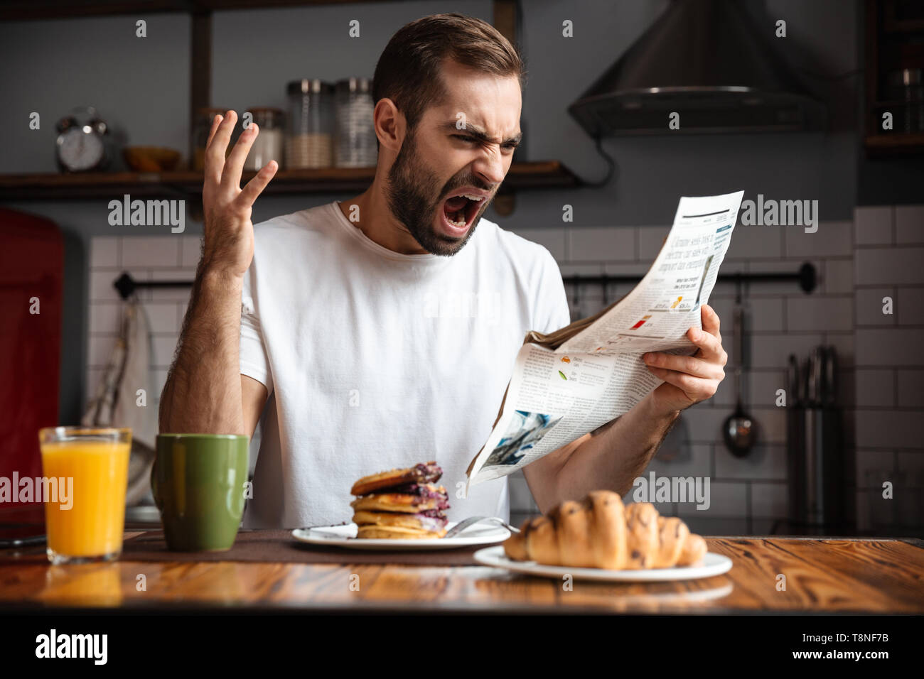 Angry shocked man having breakfast, reading newspaper - Stock Image