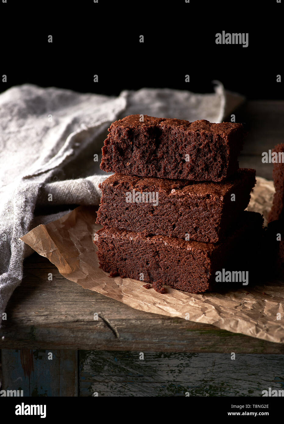 A stack of baked square pieces of chocolate brownie cake on brown parchment paper, black background - Stock Image