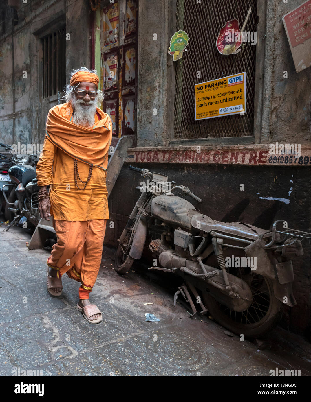 Hindu priest walks pass an abandoned motorcycle in the narrow streets of Old City of Varanasi, India - Stock Image