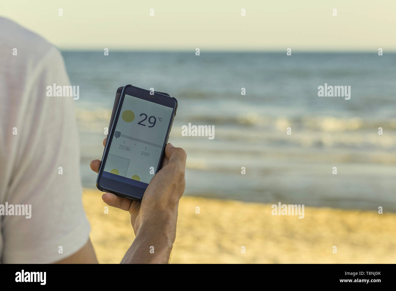 Smart phone with weather forecast on screen, smart phone dialing 20ºC at Matalascañas beach in Huelva, Andalusia, Spain - Stock Image