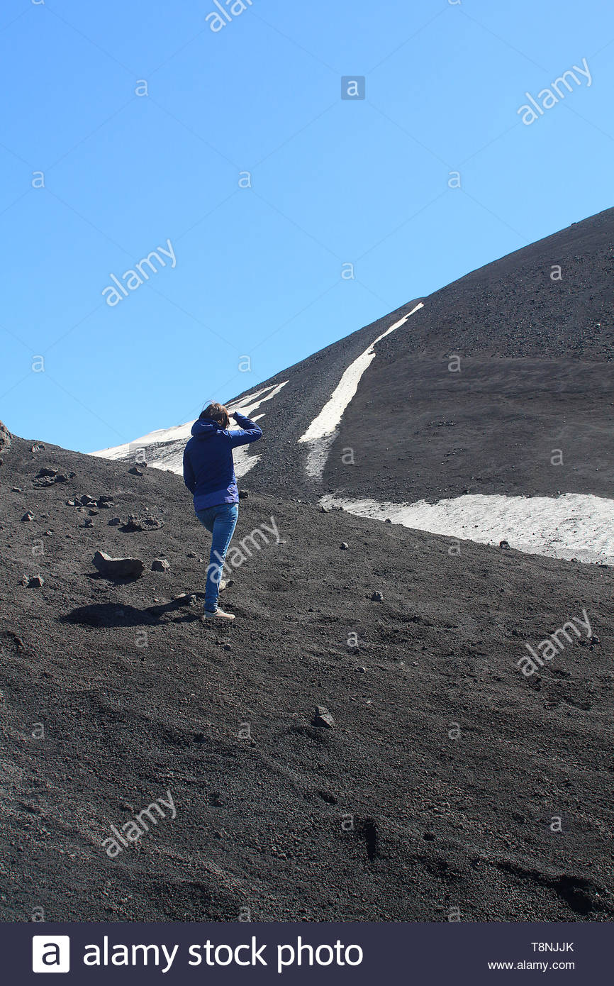 Young woman visiting Etna Park in Sicily with its black lava ash and snow fields - Stock Image