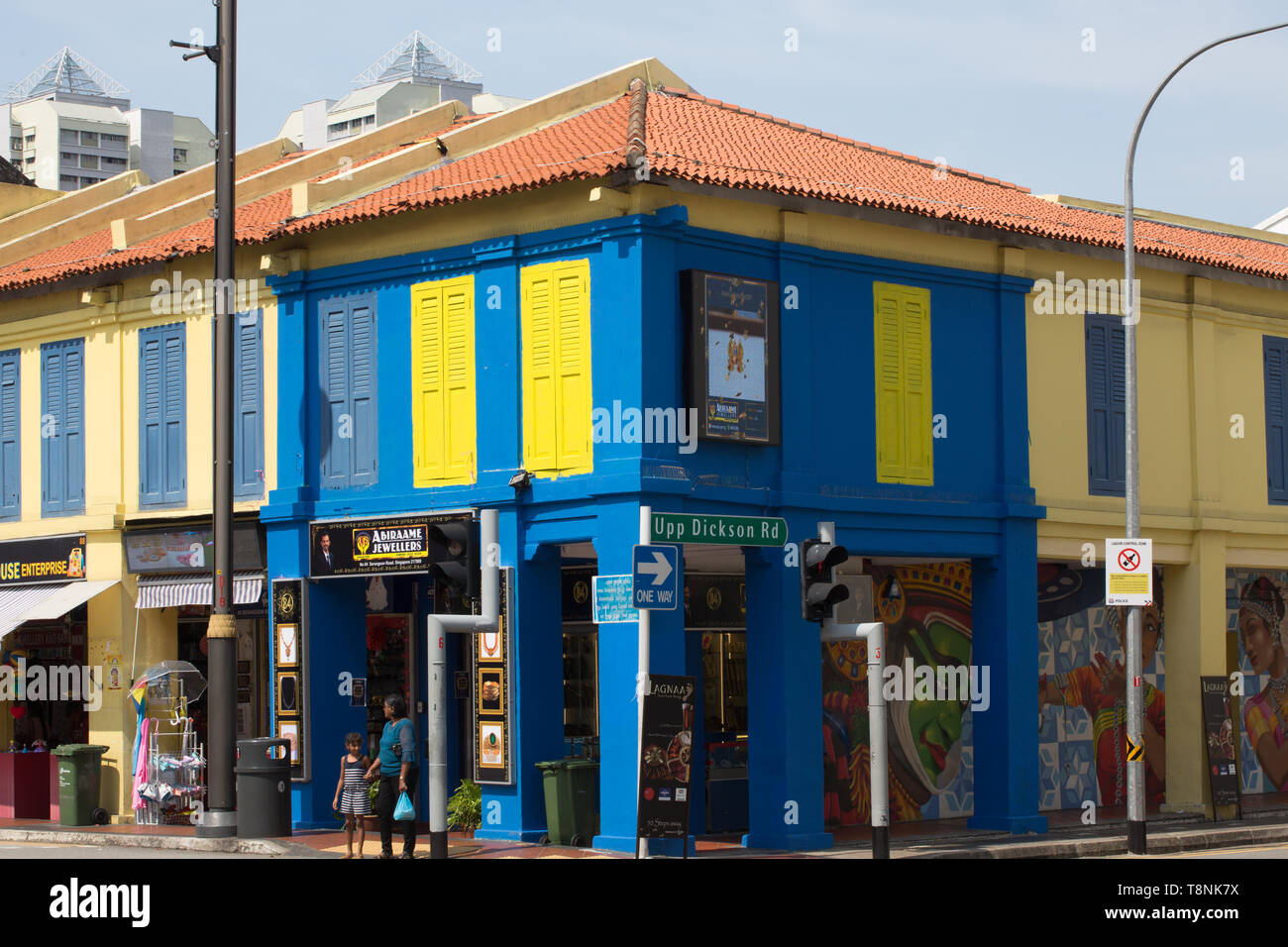 A shophouse painted in blue and wooden windows in yellow at Little India, Singapore. - Stock Image