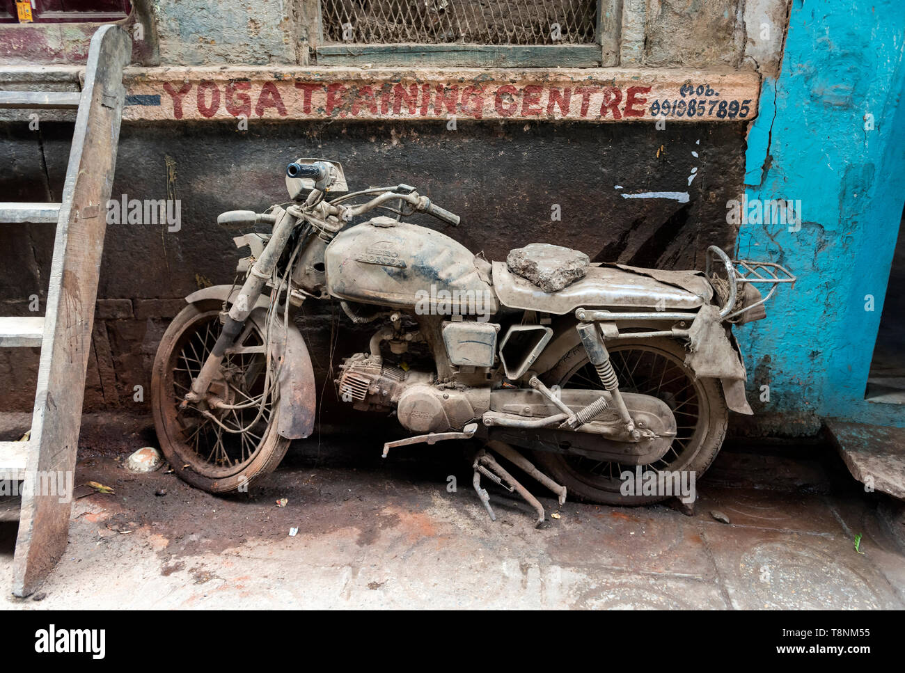 Abandoned dusted motorcycle in the streets of Varanasi Old City, India - Stock Image