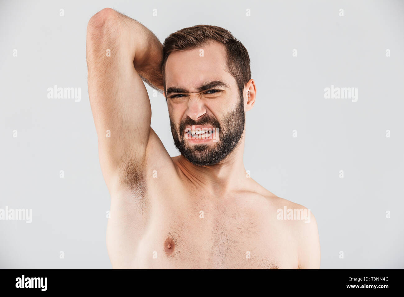 Close up portrait of a disgusted bearded man standing isolated over white background, smelling his armpit - Stock Image