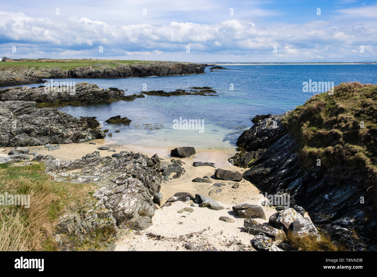 Small sandy beach in a rocky cove between Borthwen and Silver Bay, Rhoscolyn, Isle of Anglesey, Wales, UK, Britain Stock Photo