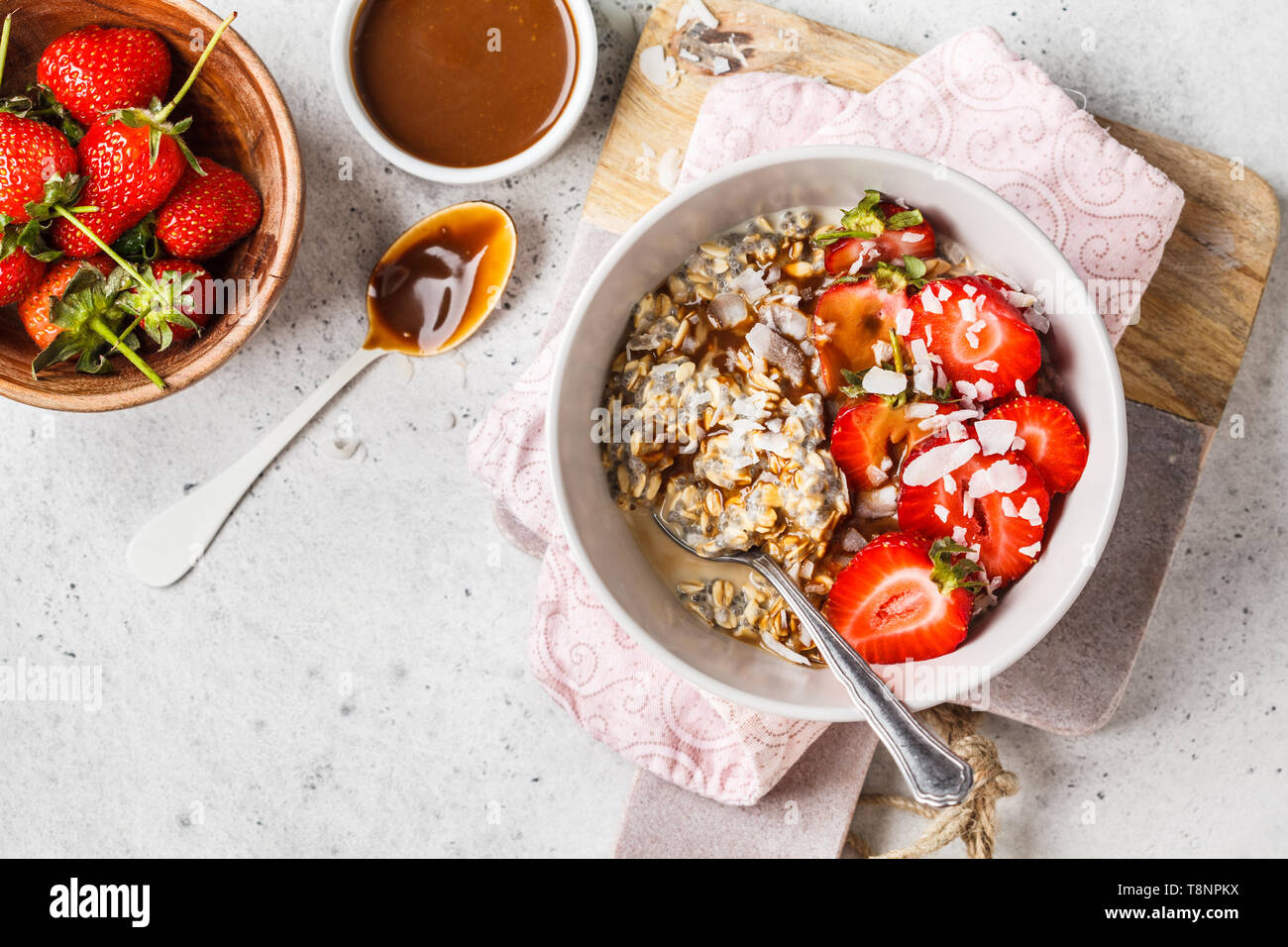 Vegan breakfast. Oatmeal with chia seeds, berries, seeds and caramel in a white bowl. Stock Photo