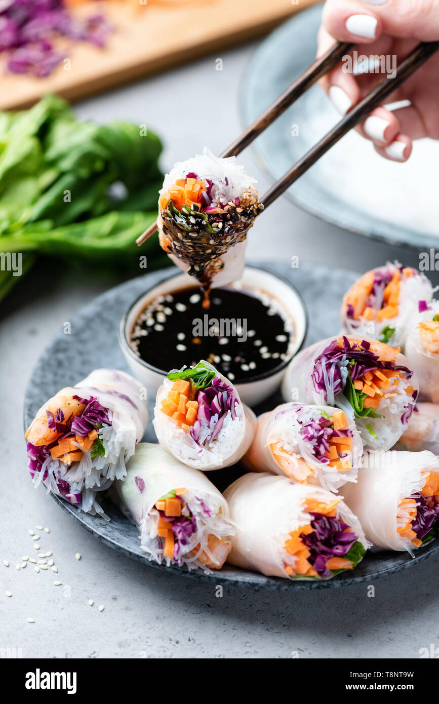 Rice paper rolls or fresh spring rolls stuffed with vegetables and shrimps. Person eating rolls, asian cuisine - Stock Image