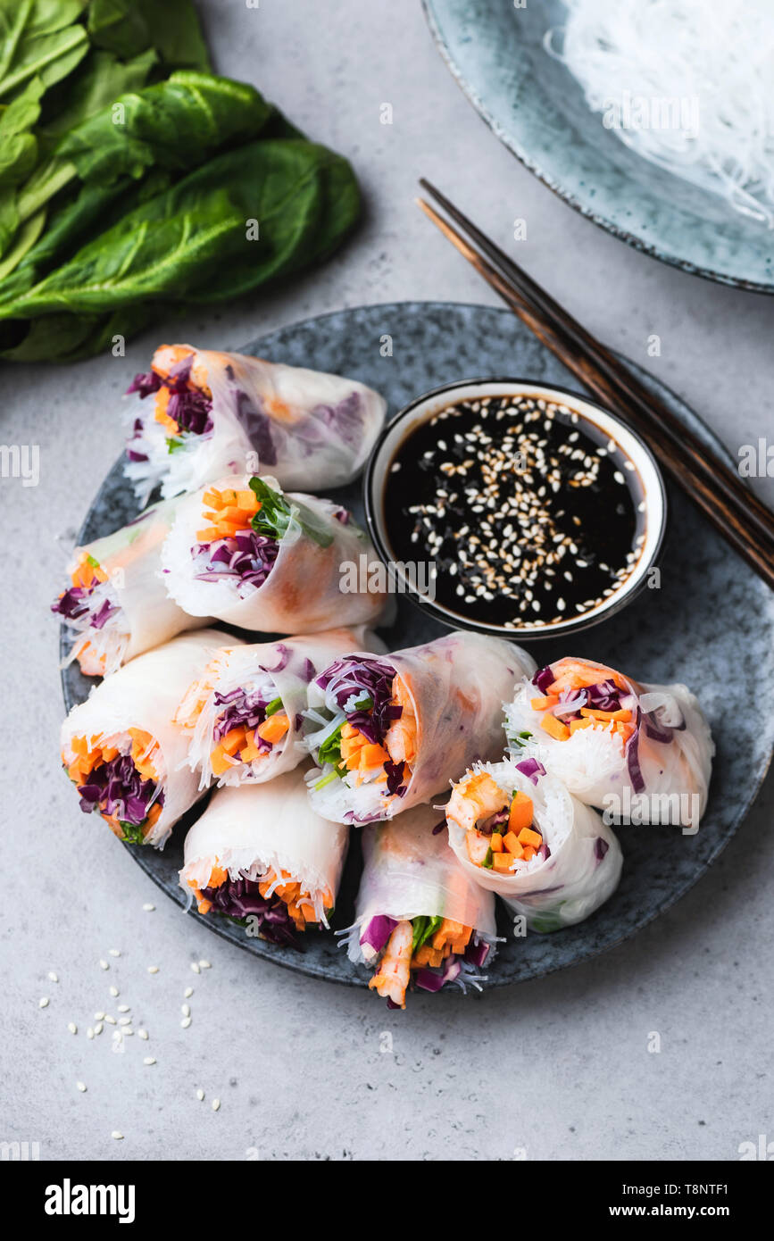 Vietnamese rice paper rolls with fresh vegetables and shrimps served with soy sauce. Healthy vegetarian appetizer. Asian cuisine food - Stock Image