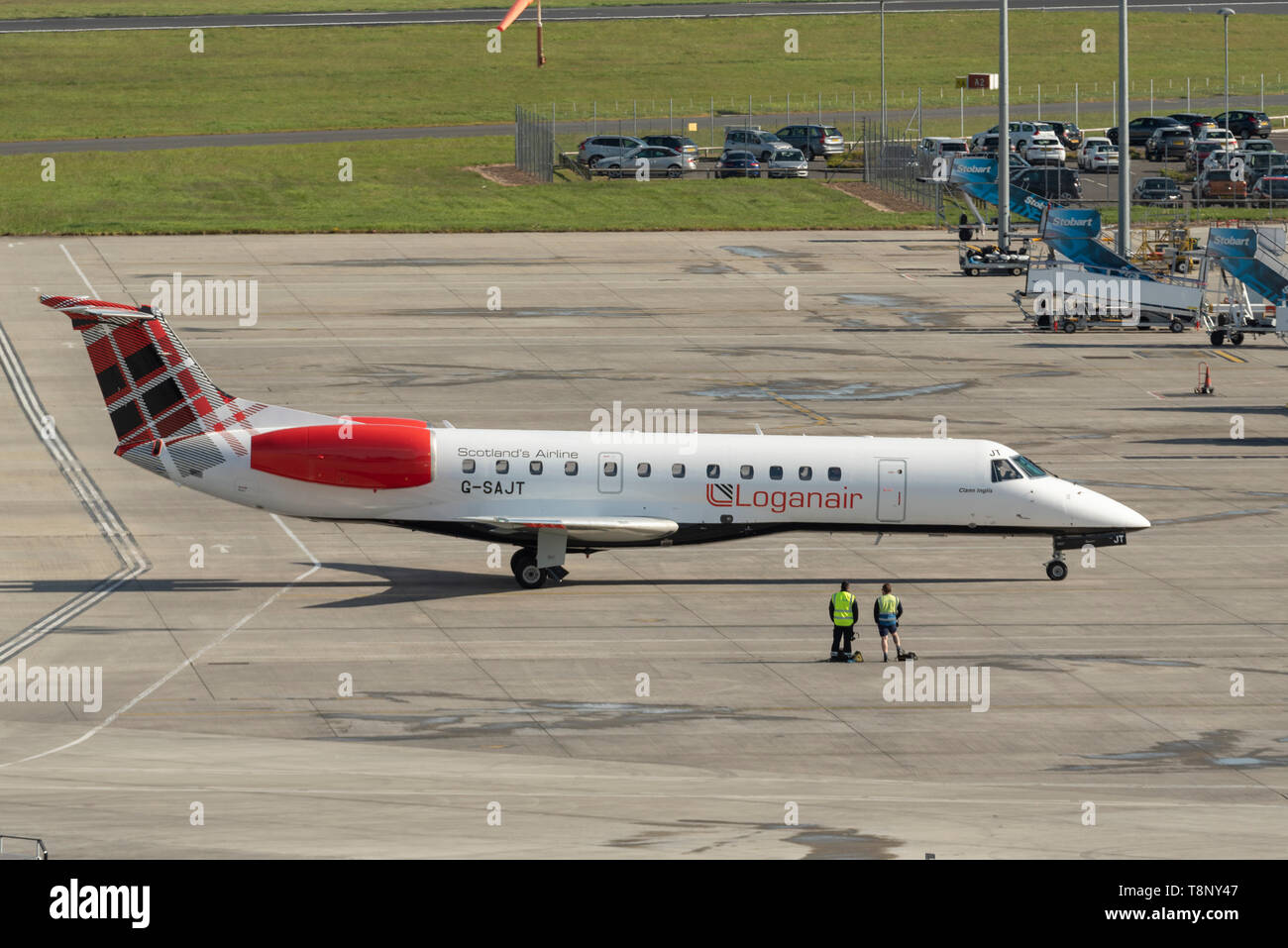 Loganair Embraer ERJ135 at London Southend Airport, Essex, UK. Tartan tail. On the apron with ground handlers Stock Photo