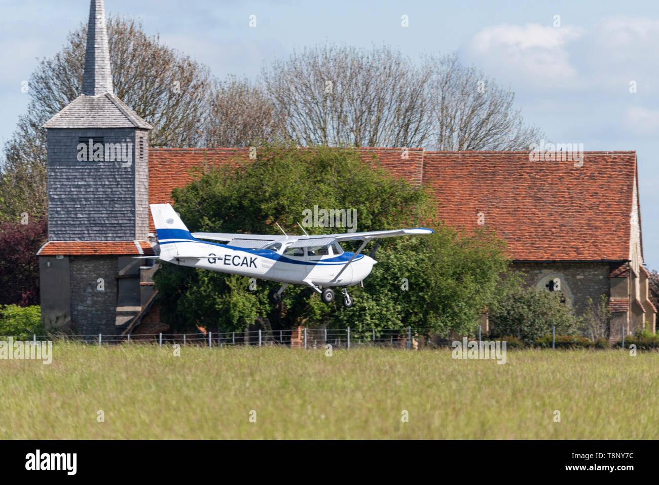 Cessna 172 Skyhawk private plane G-ECAK landing at London Southend Airport, Essex, UK. St Laurence & All Saints Church near airport - Stock Image