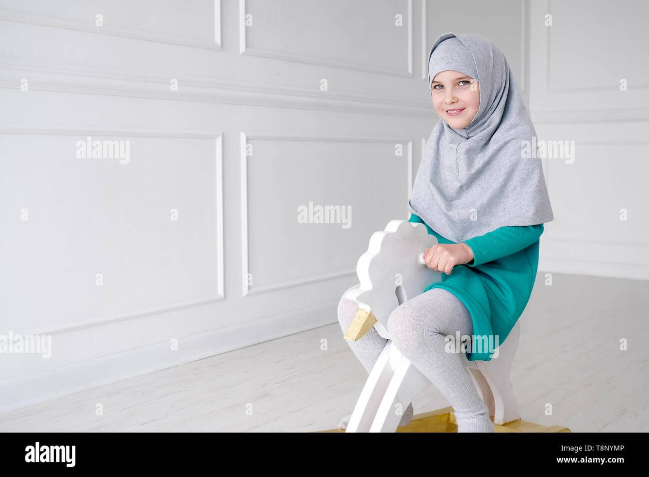 Muslim teen 9 year girl in grey hijab and blue dress is playing riding on toy horse rocking chair in her white modern room. - Stock Image