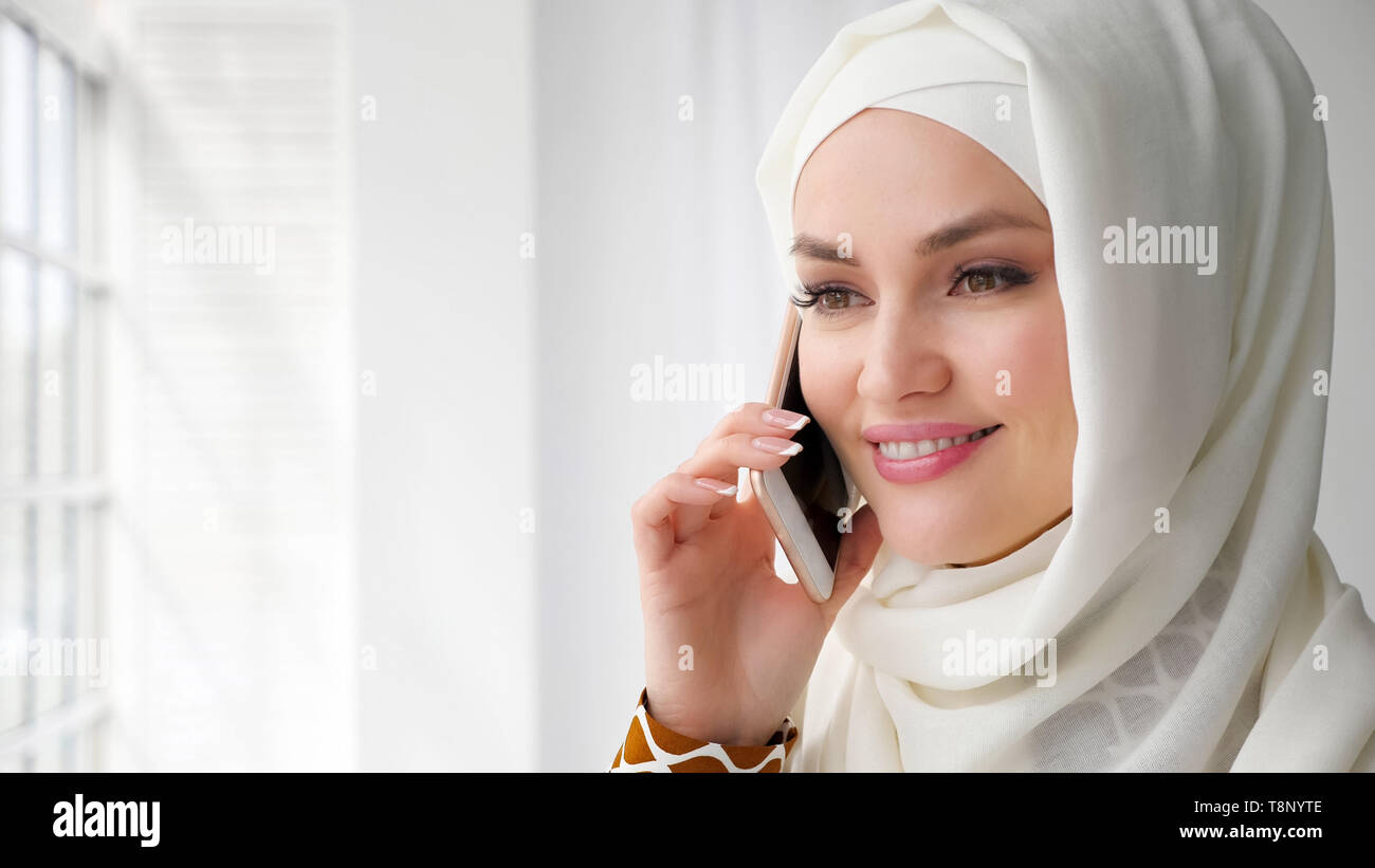 Portrait of attractive muslim woman in white hijab is talking mobile phone and smilng standing near the window, copy space - Stock Image