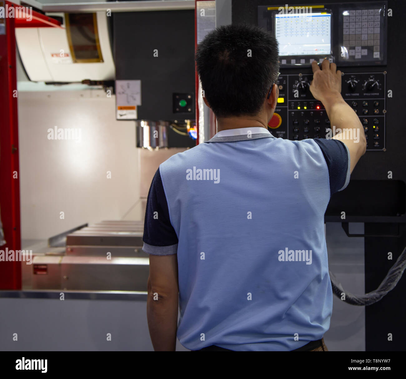Industrial worker input data to operate cnc milling machine - Stock Image
