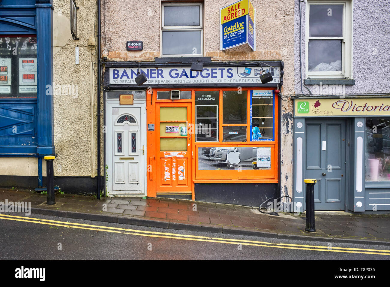 A closed down phone unlocking shop with an unsuitable UPVC plastic door adjacent - Stock Image