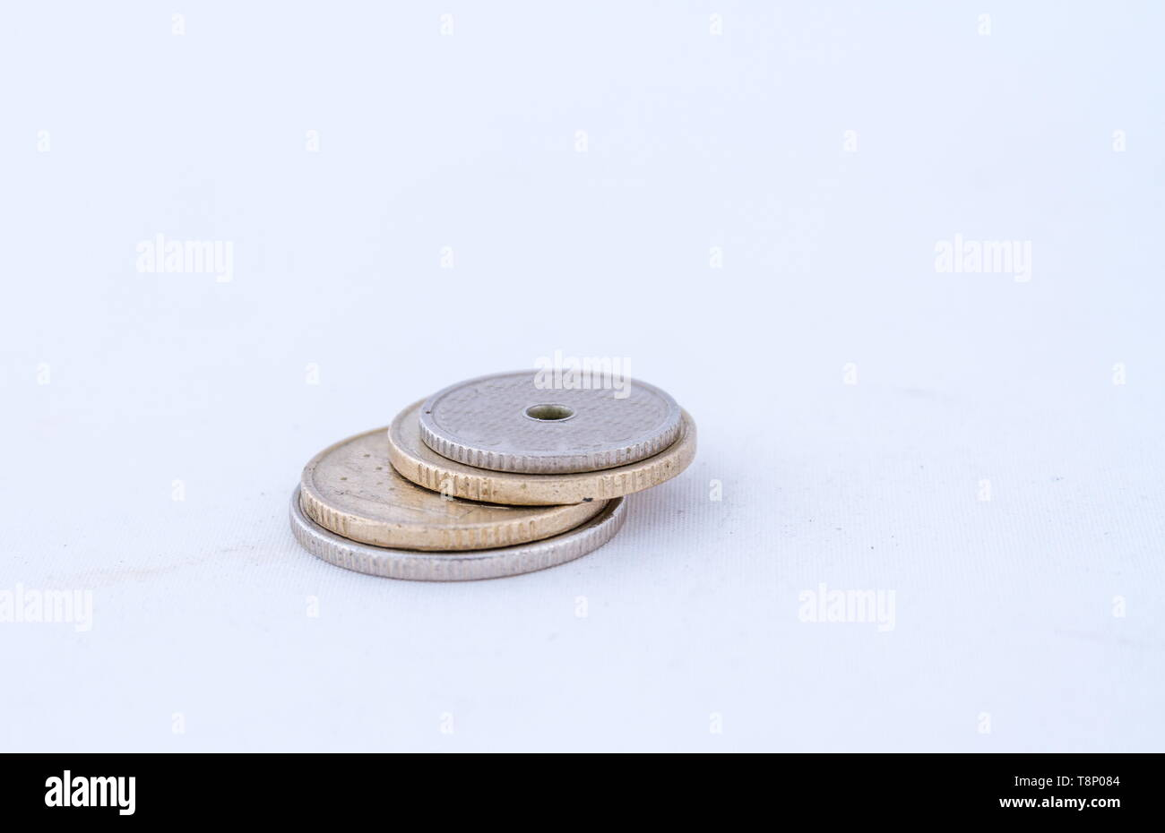 A small stack of coins isolated on a white background image with copy space in landscape format - Stock Image
