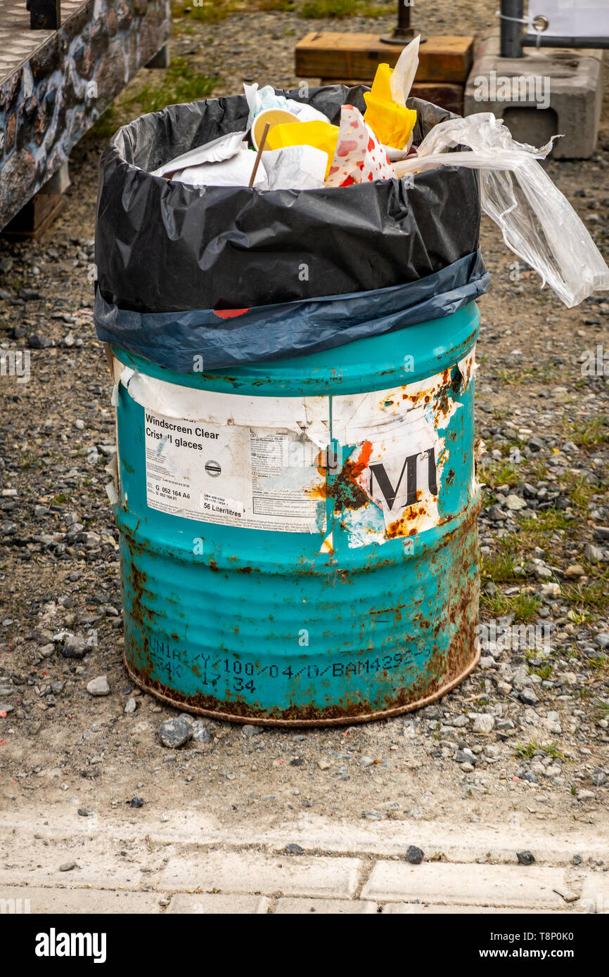 Braunschweig, Germany, May 5., 2019: Ugly dirty old rusty garbage can improvised from a tin can, with a plastic bag filled with fresh garbage - Stock Image