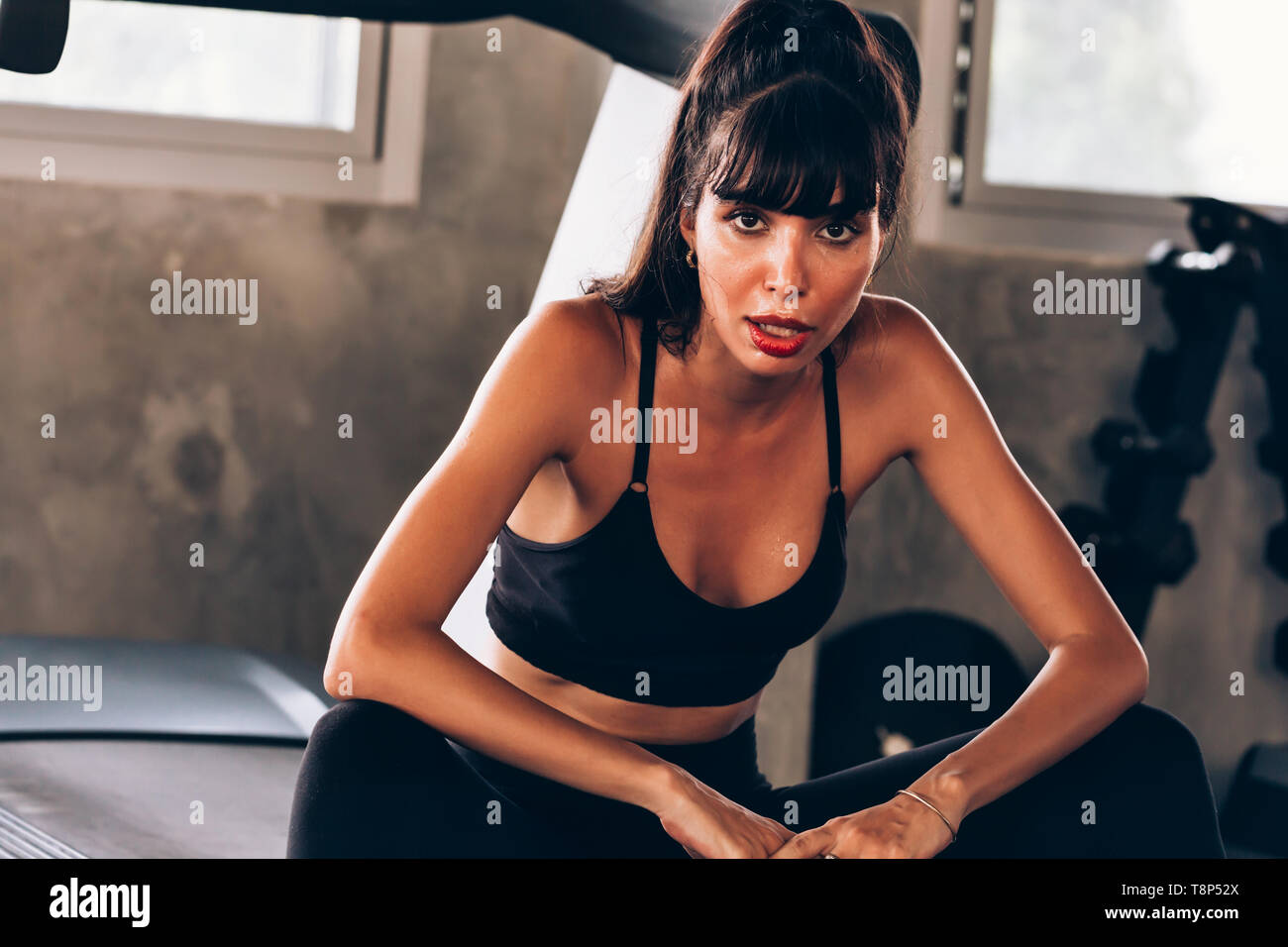 Young Caucasian beautiful female fitness model on sweat wearing sportswear and sitting on treadmill in gym. Health and sports portrait concept - Stock Image