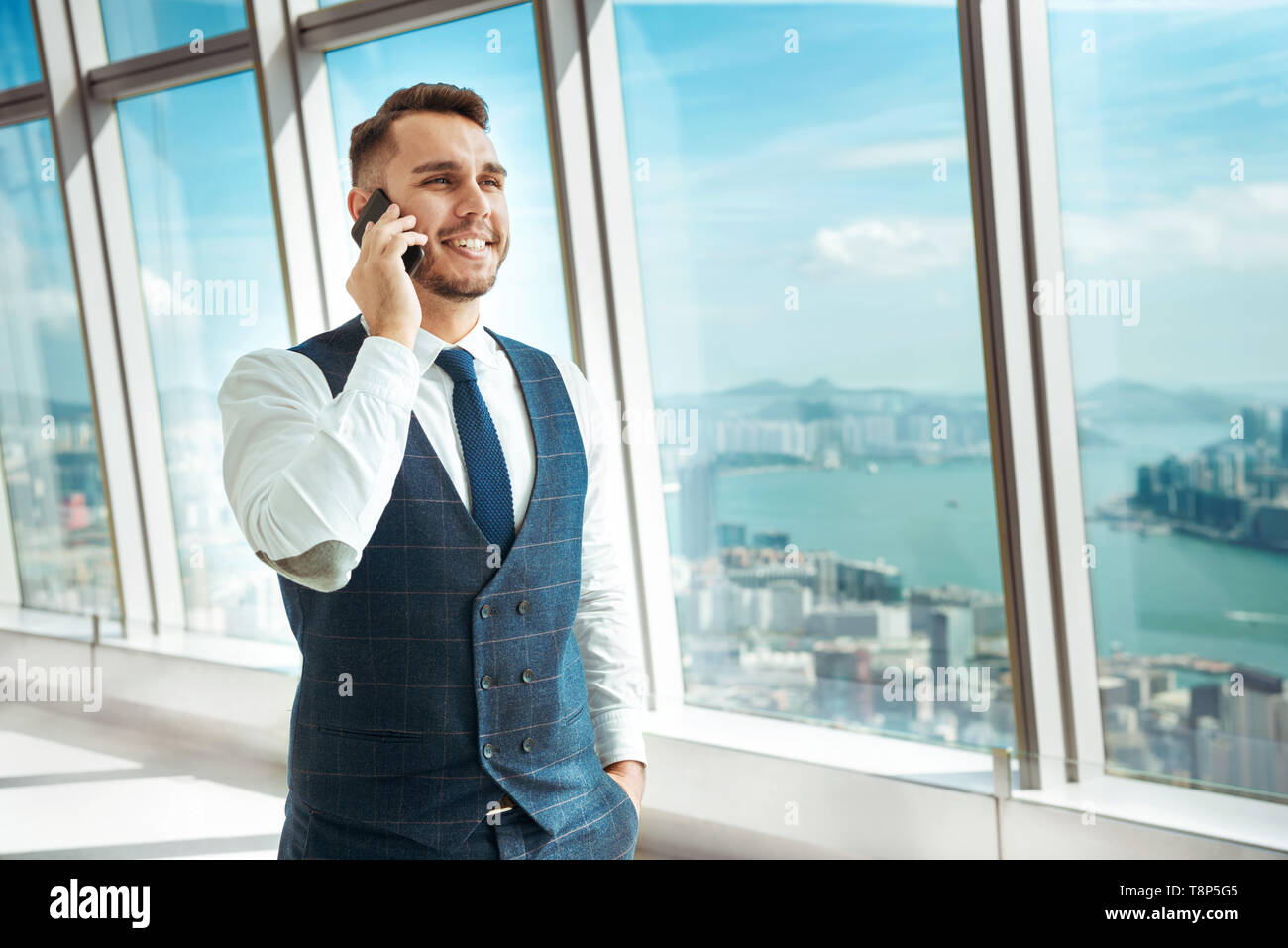 Successful businessman speaks by mobile phone against big city Stock Photo