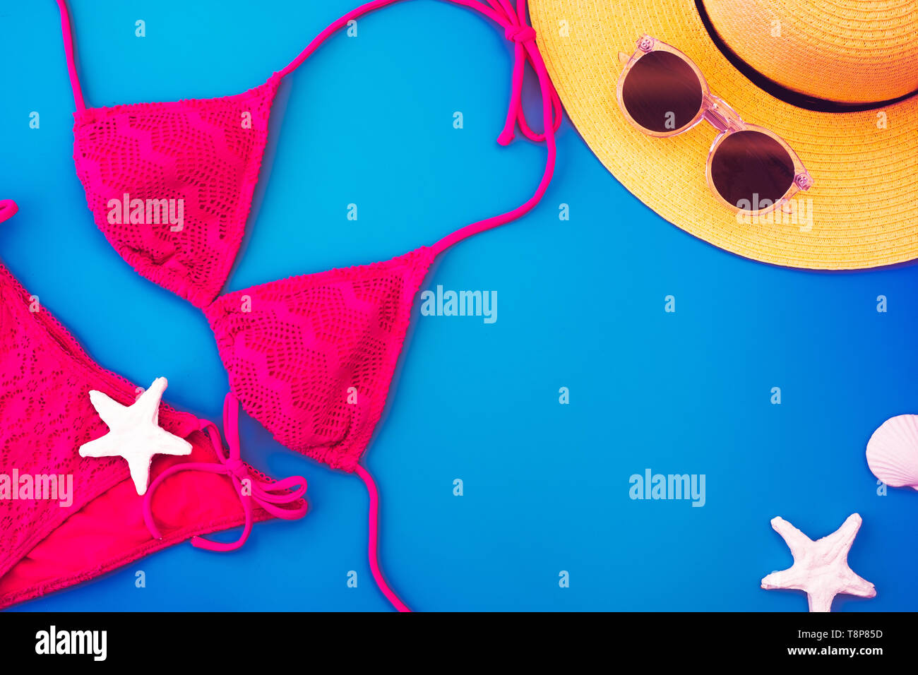 Top view yellow summer hat and bikini, bikini,sunglasses,seashell on vivid blue background.Summer vacation holiday backdrop.copy space for adding text - Stock Image