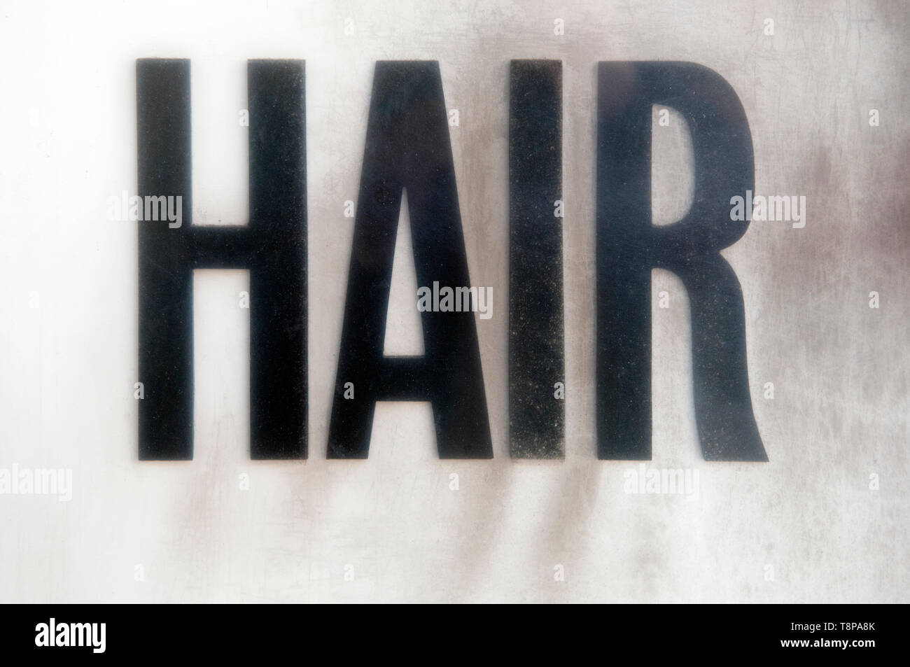 The Word Hair In Bold Black Lettering On A Grubby Frosted Background - Stock Image