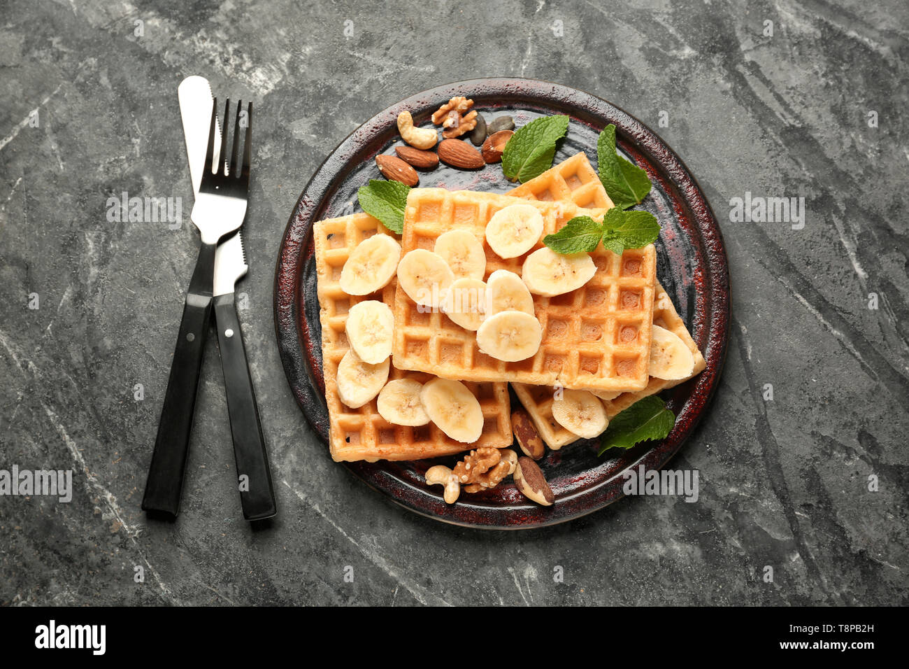 Delicious waffles with banana slices and nuts on dark table - Stock Image