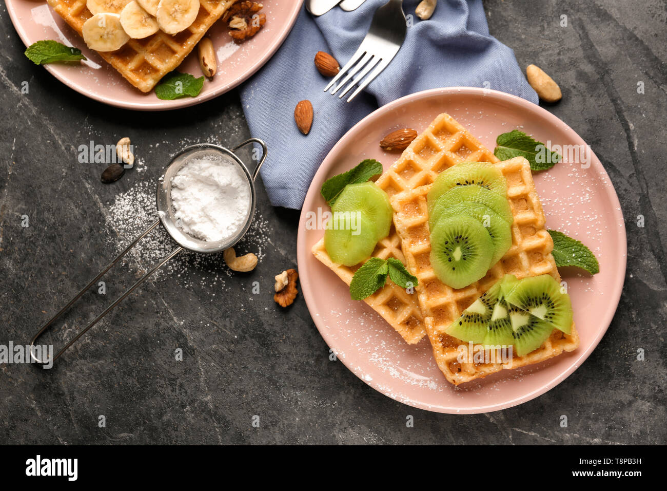 Delicious waffles with kiwi slices on dark table - Stock Image