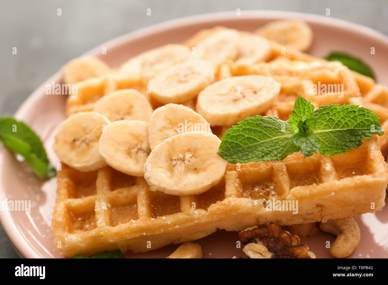 Delicious waffles with banana slices and nuts on plate, closeup - Stock Image
