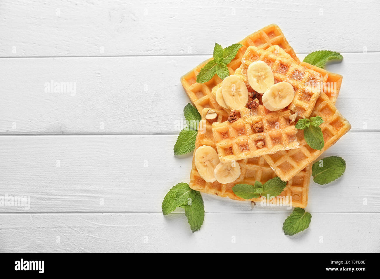 Delicious waffles with banana slices on white wooden table - Stock Image