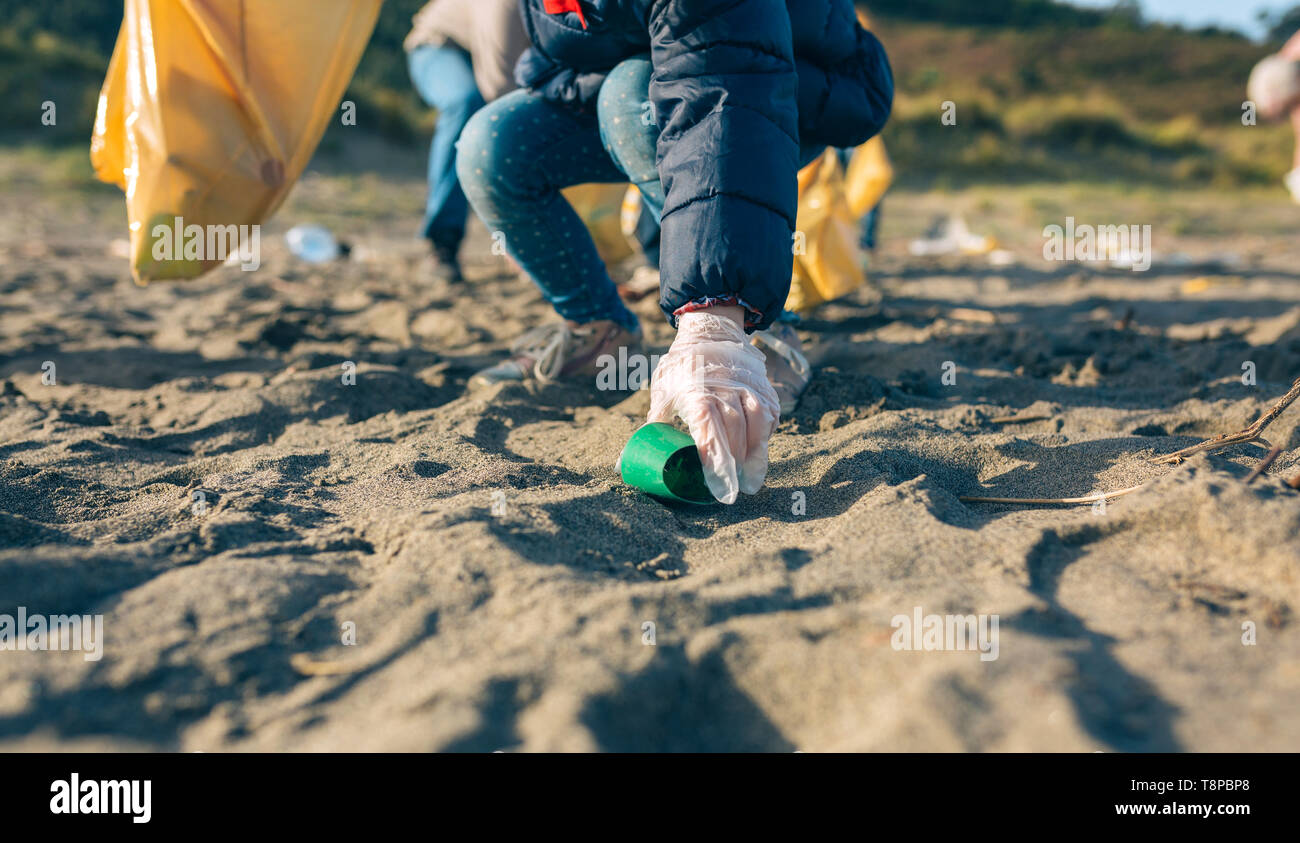 Little girl cleaning the beach - Stock Image