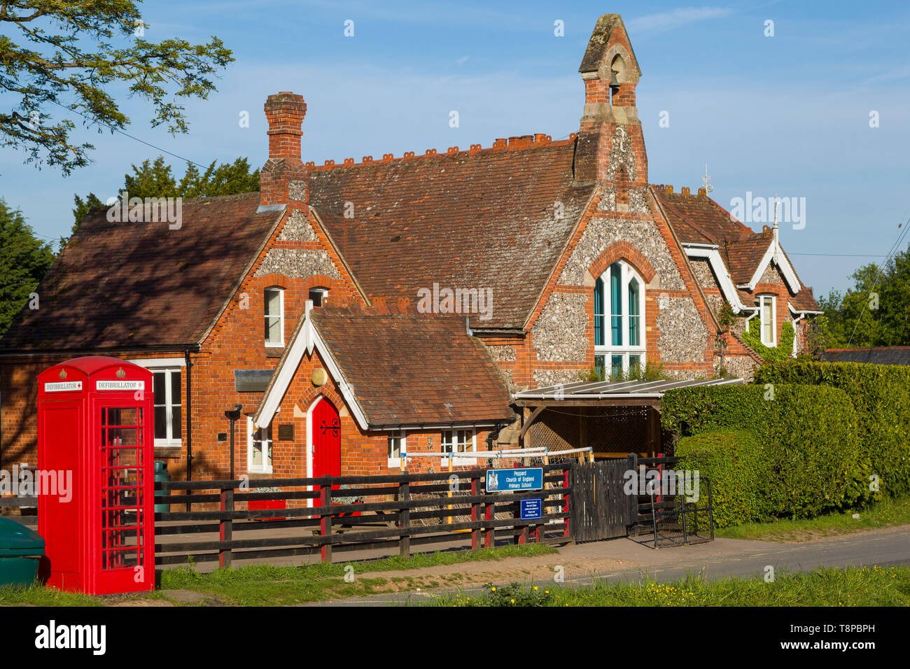 Traditional Victorian brick and flint school building, still in use at Peppard, Oxfordshire with a red telephone box converted for a defibrillator - Stock Image