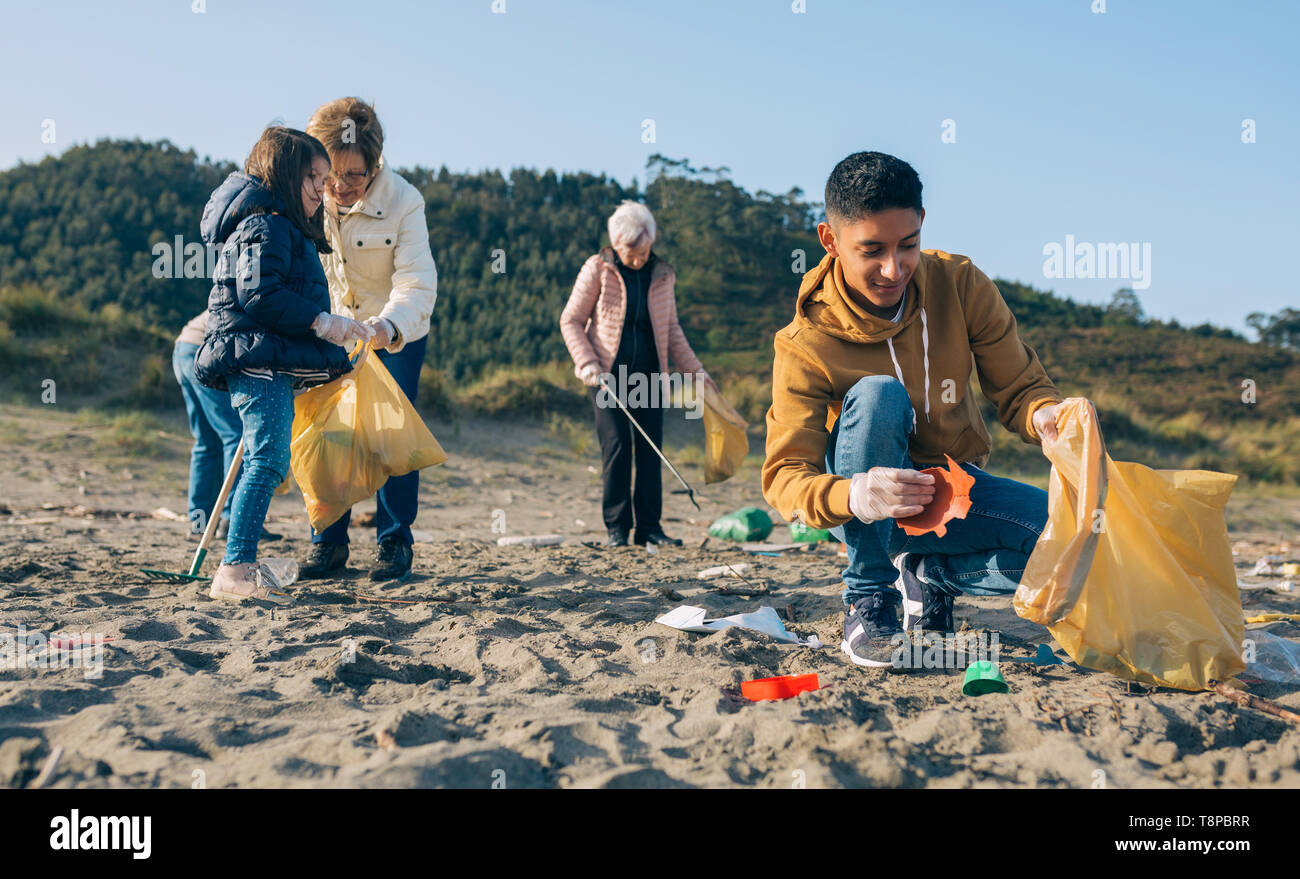 Young man cleaning the beach - Stock Image