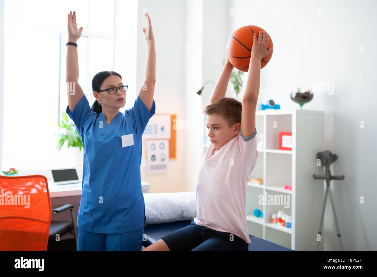 Serious professional physical therapist raising her hands - Stock Image