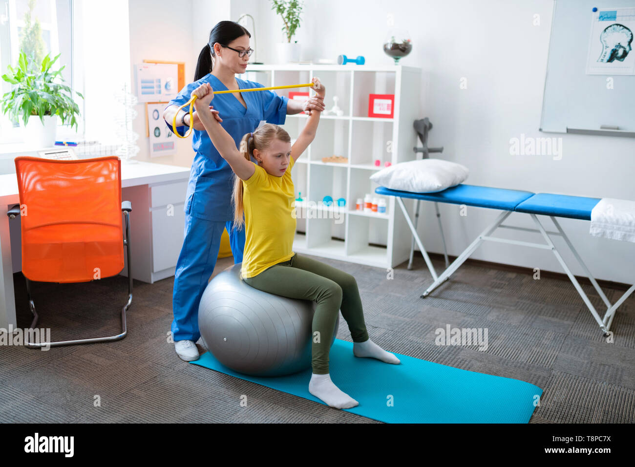 Attentive long-haired therapist improving exercise of blonde girl - Stock Image