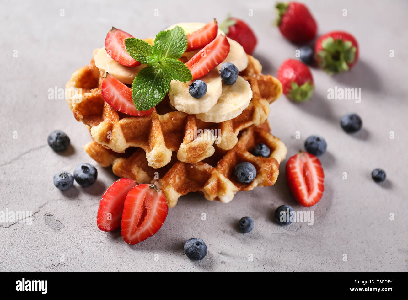 Delicious waffles with berries and banana on grey table - Stock Image