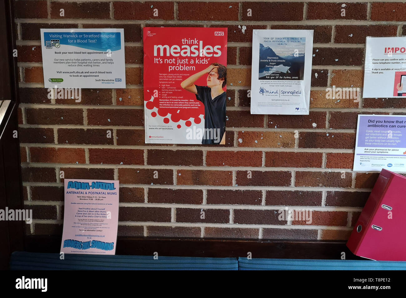 A poster with advice for patients about measles is seen in an NHS local doctors surgery waiting room in Warwickshire, UK, On May 14, 2019. Stock Photo