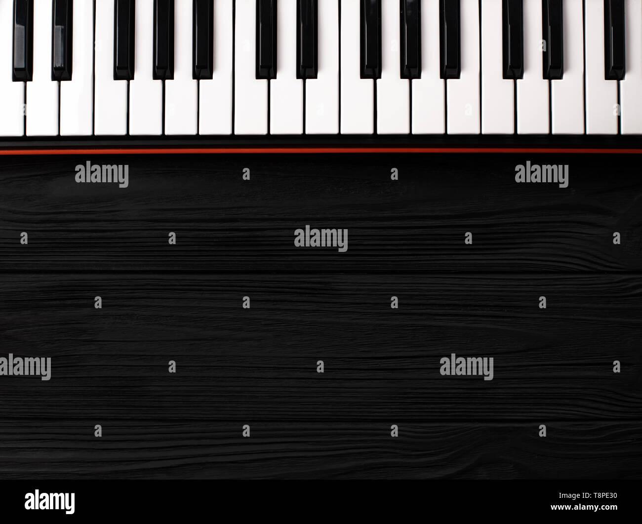 synthesizer keyboard on black wooden background - Stock Image