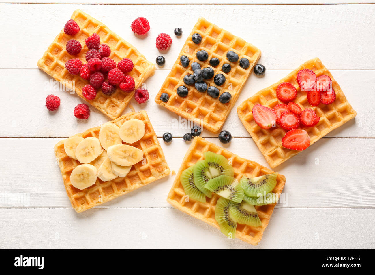 Delicious waffles with fruits and berries on white wooden background - Stock Image